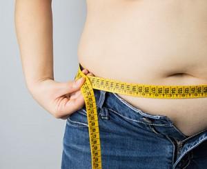 Maßband um Bauch, Übergewicht begünstigt Sodbrennen