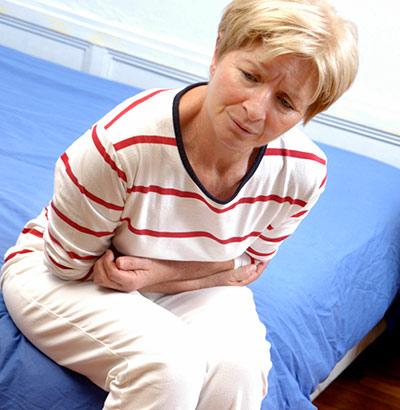 Frau mit Durchfall sitzt auf Bett und hält sich den Bauch