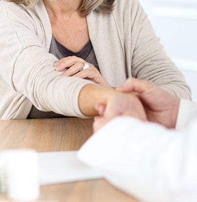 Arzt fühlt den Puls einer Frau – bei Durchfall sind meist nicht viele Untersuchungen nötig