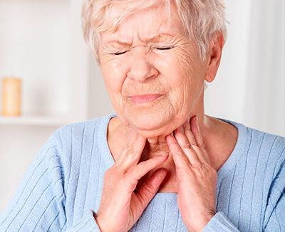 Frau mit schmerzverzerrtem Gesicht fasst sich an den Hals, Schmerzen beim Schlucken sind bei Sodbrennen ein Alarmzeichen