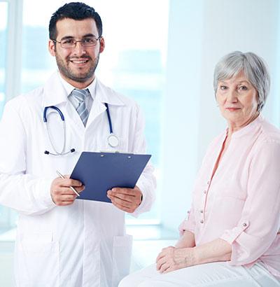 : Arzt mit älterer Patientin bei der Morbus Crohn-Diagnose