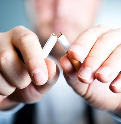 Mann zerbricht Zigarette – bei Morbus Crohn das Rauchen aufgeben