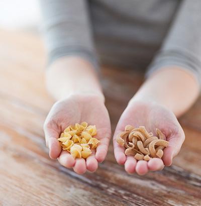 Zwei Nudelsorten in der Hand – Gluten ist Auslöser der Zöliakie-Symptome