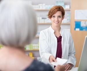 Apothekerin nimmt Rezept für Abführmittel entgegen