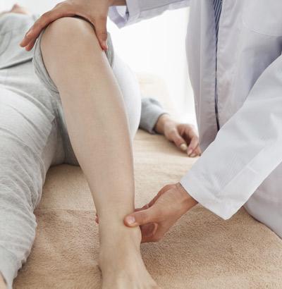 Arzt untersucht Knie im Rahmen der Colitis ulcerosa-Diagnose