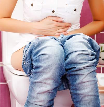 Frau auf Toilette legt Hände auf den Bauch