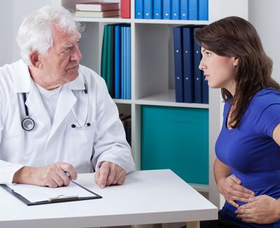 Arzt befragt Patientin mit Blähbauch, um die Diagnose zu stellen