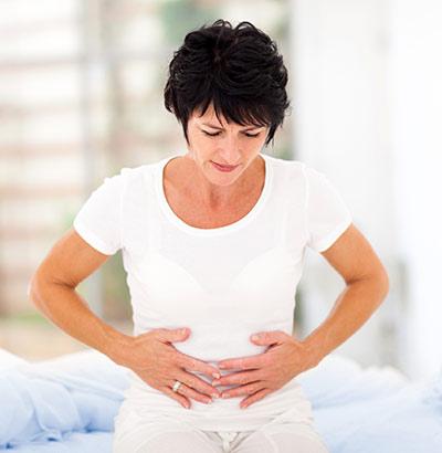 Frau hält sich Bauch - Reizdarm verursacht unter anderem Bauchschmerzen