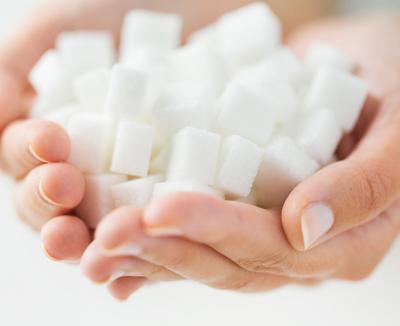 Hände halten Zuckerwürfel - Diabetes gehört zu den Blähbauch-Ursachen