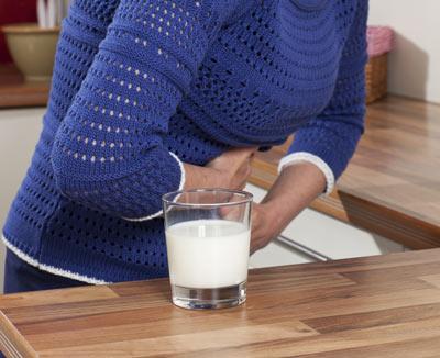 Frau mit Bauchschmerzen nach Milchkonsum – Laktoseintoleranz gehört bei Bauchschmerzen zu den möglichen Ursachen
