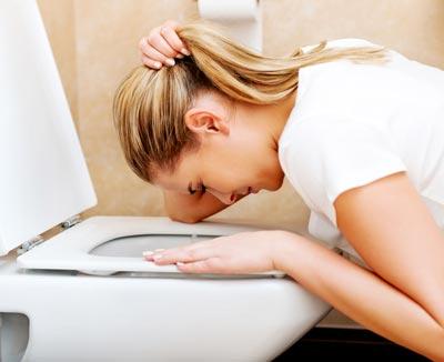 Frau erbricht in Toilette – Erbrechen und Übelkeit sind häufig gleichzeitig auftretende Symptome