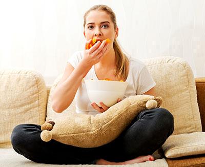 Völlegefühl - Frau isst hastig vor dem Fernseher