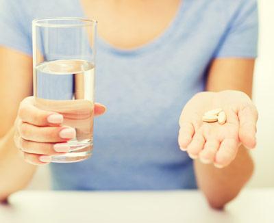 Frau nimmt Schmerzmittel - mögliche Magenschmerzen-Ursachen